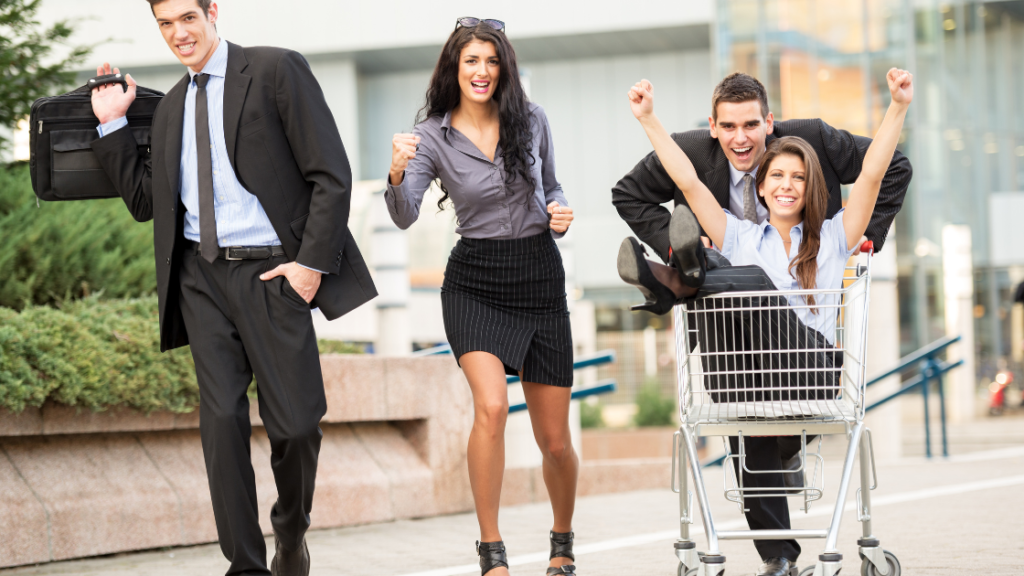 Men and women smiling, girl sitting in the shopping cart while man is pushing the cart