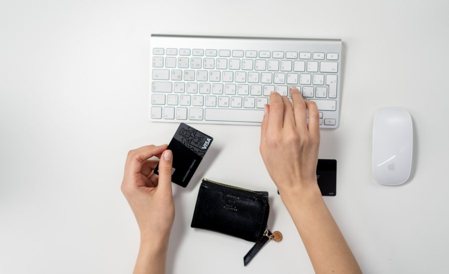 person typing on computer keyboard with right hand while holding a black visa card on left hand
