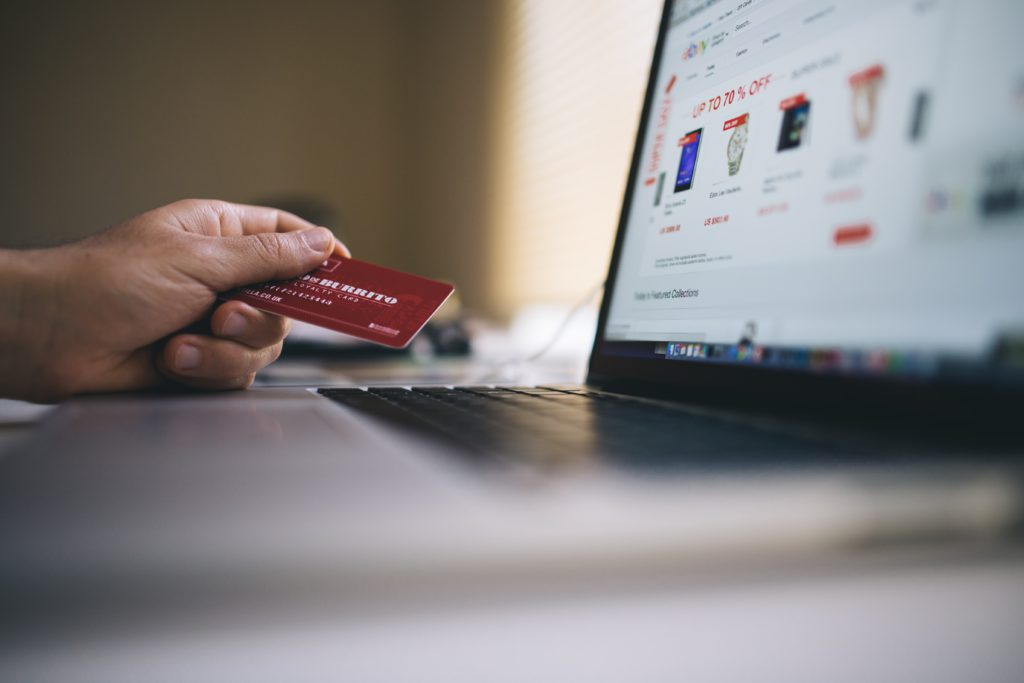 Person holding a card while shopping online using a laptop