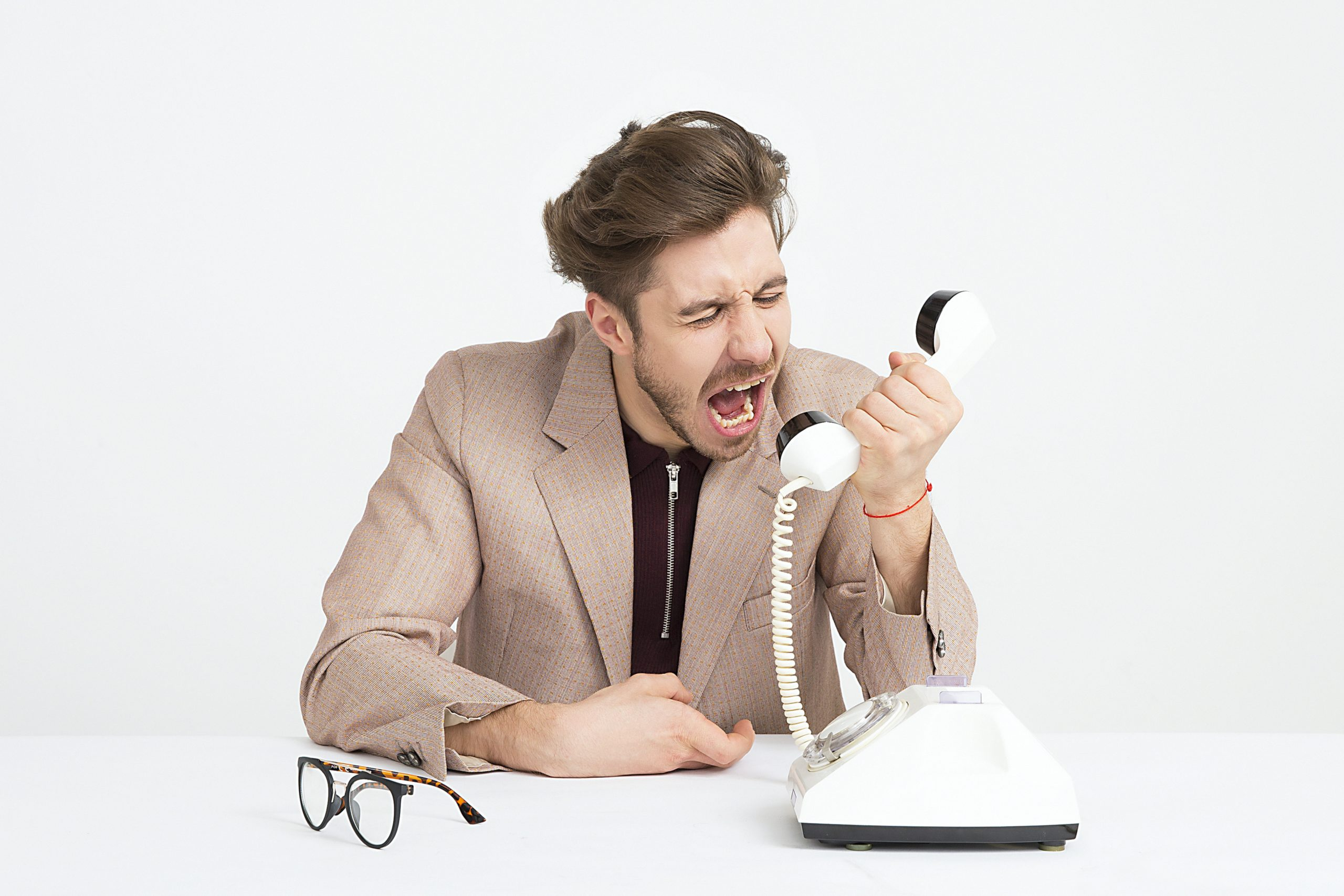 angry man on phone, white background, white phone, eyeglasses on the desk